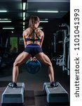 Small photo of Strong, muscular, girl in black shorts, doing a squat with a pancake from the bar, legs wide apart. Dark gym.