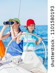 Small photo of Boy captain with his sister on board of sailing yacht on summer cruise. Travel adventure, yachting with child on family vacation. Kid clothing in sailor style, nautical fashion.