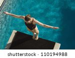 High angle view of a female diver ready to dive while standing at the edge of the springboard - stock photo