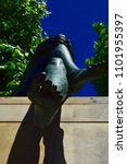 Small photo of BERLIN, GERMANY - MAY 20, 2018: Feet and legs of the sculpture DREI MÄDCHEN UND EIN KNABE at the river Spree from the artist Fritzenreiter. Deep blue sky, trees and a piece of wall. Low angle view.