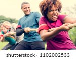 team competing in tug of war | Shutterstock . vector #1102002533
