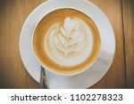 coffee cup on a wood table in... | Shutterstock . vector #1102278323