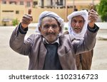 Small photo of DJELFA , ALGERIA - Mai 2017 : two men smiling with like hand wearing traditional algerian clothes captured on the street of Djelfa , Algeria
