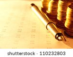 stacks of coins with numbers on documents - stock photo
