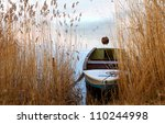 View between tall aquatic reeds and grasses to a small rowboat moored on the lakeshore in a mirror calm lake - stock photo