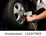 Auto mechanic changing car wheel - stock photo