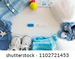 Small photo of Different baby accessories with pregnancy test. Maternal concept. Baby things, sneakers, clothes, diapers, shoes