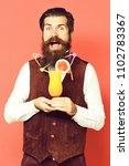 Small photo of handsome bearded man with colorful tubes in long beard and mustache has stylish hair on smiling face holding glass of alcoholic cocktail in vintage suede leather waistcoat on red studio background.
