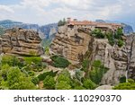 Monastery from Meteora-Greece with large green garden between tall and brown rocks - stock photo