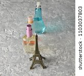 Small photo of Perfume bottles, a statuette of the Eiffel Tower on a gray concrete background.