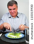 Reforming/Overweight man tries healthy dinner with notable lack of enthusiasm - stock photo