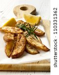 Oven baked potato wedges on a board, with fresh rosemary and lemon. - stock photo