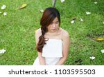 Small photo of A girl in white dress sitting on the green sward with absent-mindedness