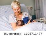 mom breastfeeding her newborn... | Shutterstock . vector #1103711477