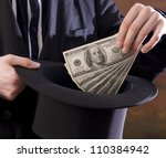 magician holding US currency and tophat - stock photo