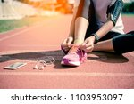 hands of a young woman shoelace ... | Shutterstock . vector #1103953097