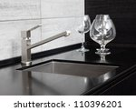 Modern kitchen sink with metal tap and black marble - stock photo