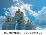 Small photo of large beautiful Orthodox Church with Golden domes against a blue sky and clouds. Russia, Saransk city, Cathedral of the Holy warrior Fyodor Ushakov.
