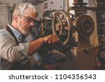 an elderly man at work in a... | Shutterstock . vector #1104356543