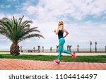 girl runs on the sea embankment.... | Shutterstock . vector #1104414497