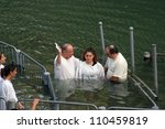 YARDENIT , ISRAEL - SEPTEMBER 30: Baptismal site at Jordan river shore. Baptism of pilgrims  in Yardenit, Israel on September 30, 2006. - stock photo