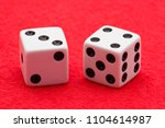 Small photo of Horizontal Photo of Two white dice with black dots displaying craps seven on two sides on red felt background