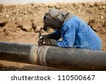 Male welder worker wearing protective clothing fixing welding and grinding industrial construction oil and gas or water and sewerage plumbing pipeline outside on site - stock photo