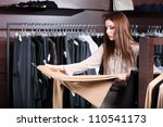 Small photo of Attractive woman is looking for a perfect cloth which is all the rage