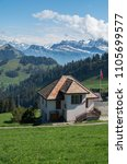 Small photo of House at the top of mount rigi with a flag pole in the foreground and the alps in the background