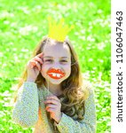 Small photo of Girl sits on grass at grassplot, green background. Child posing with cardboard smiling lips and crown for photo session at meadow. Humour queen concept. Girl on cheerful face spend leisure outdoors.