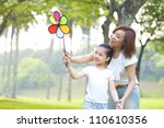 Asian family playing windmill at outdoor park - stock photo