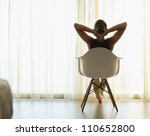 Female sitting in front of window. Rear view - stock photo