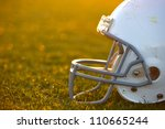 American Football Helmet on the Field with room for copy backlit by the setting sun - stock photo