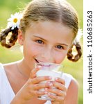 Healthy kid, milk - Portrait of lovely girl drinking fresh milk outdoors - stock photo