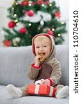 Baby in deer suit with Christmas present box eating cookie - stock photo