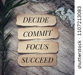 Small photo of Motivational and inspirational quote - 'Decide, commit, focus, succeed' written on pieces of papers . With vintage styled background.