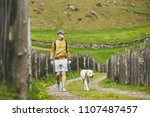 tourist with dog in countryside.... | Shutterstock . vector #1107487457
