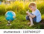 a little blond boy holding a... | Shutterstock . vector #1107604127