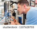 Small photo of Male Engineer Working On Machine In Factory