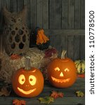 Two smiling jack-o-lanterns on a wooden deck - stock photo