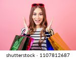 Small photo of portrait of a stylish and attractive crazy shopaholic woman in striped sweater holding a lot of shopping bags surprised and shocked on a pink background in the studio. concept of shopaholism and sale