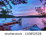 Sunset on the lake with a boat, trees, walkways and benches in Finland - stock photo