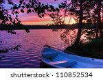 Sunset on the lake with a boat and trees in Finland - stock photo