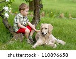 A little boy and dog on garden - stock photo