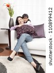 mother and girl smiling in the room - stock photo