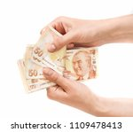 Small photo of Hands holding Turkish lira bills isolated on white background. Counting or spend money.