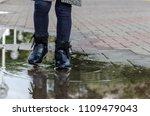 a child walks through puddles ... | Shutterstock . vector #1109479043