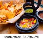 Pico de gallo and dipping sauce with a basket of nacho chips - stock photo