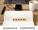 Small photo of Closeup on notebook over vintage desk surface, front focus on wooden blocks with letters making Error text. Business concept image with office tools and coffee cup in background