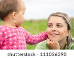 Young mother and her baby girl playing while outdoors on a walk - stock photo